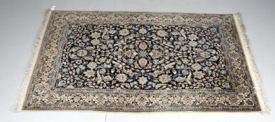 A Nain style rug with dark blue field with repeating bird and foliage decoration