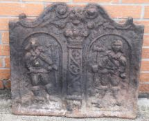 A cast iron fire back- with 17th century style decoration of two standing cavaliers
