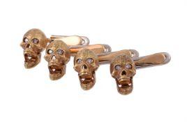 A set of four diamond set skull dress studs by William & Son