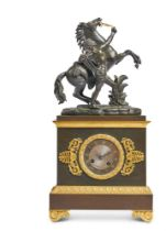 AN EMPIRE STYLE FRENCH BRONZE AND GILT METAL MANTEL CLOCK WITH A MARLY HORSE