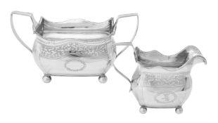A George III Irish silver oblong baluster sugar bowl and cream jug
