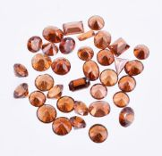 † A packet of mixed cut hessonite garnets