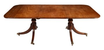 A mahogany twin pedestal dining table with one loose leaf in Regency style