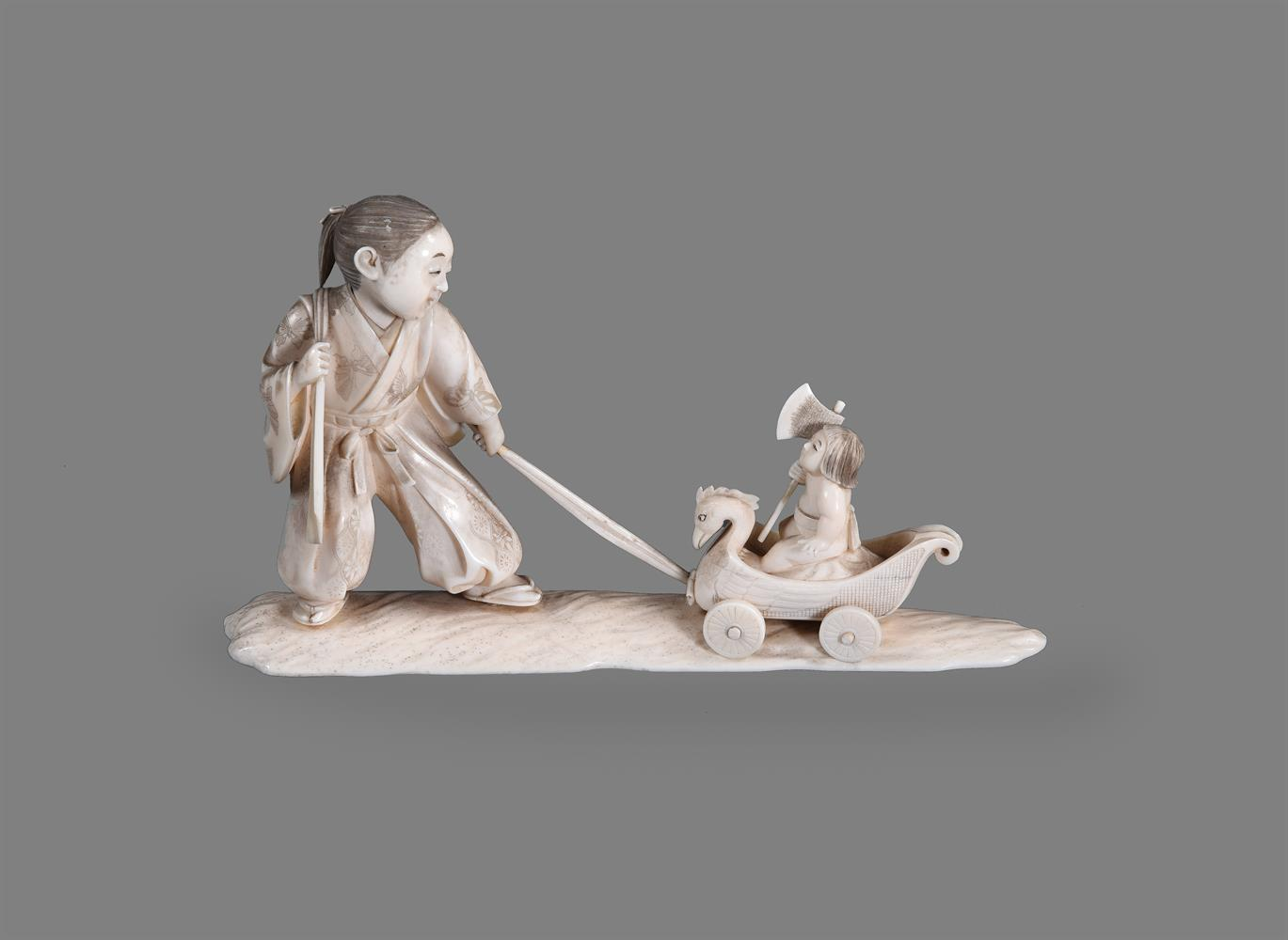 Y A Japanese Ivory Okimono of a young man standing on a shaped base