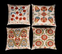 A set of four embroidered cushions in suzani style