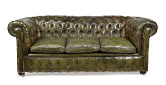 A green leather upholstered sofa