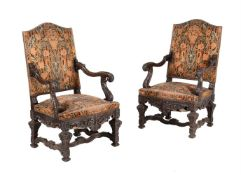 A pair of carved walnut and upholstered armchairs in mid 18th century style