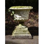 A composition stone urn on stepped base