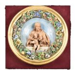 An Italian glazed and biscuit pottery relief moulded roundel in the Della Robia style