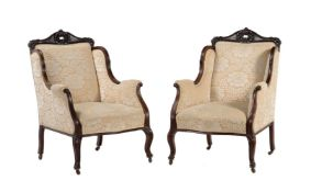 A pair of late Victorian mahogany and upholstered armchairs