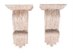 A pair of carved and white painted wood wall brackets