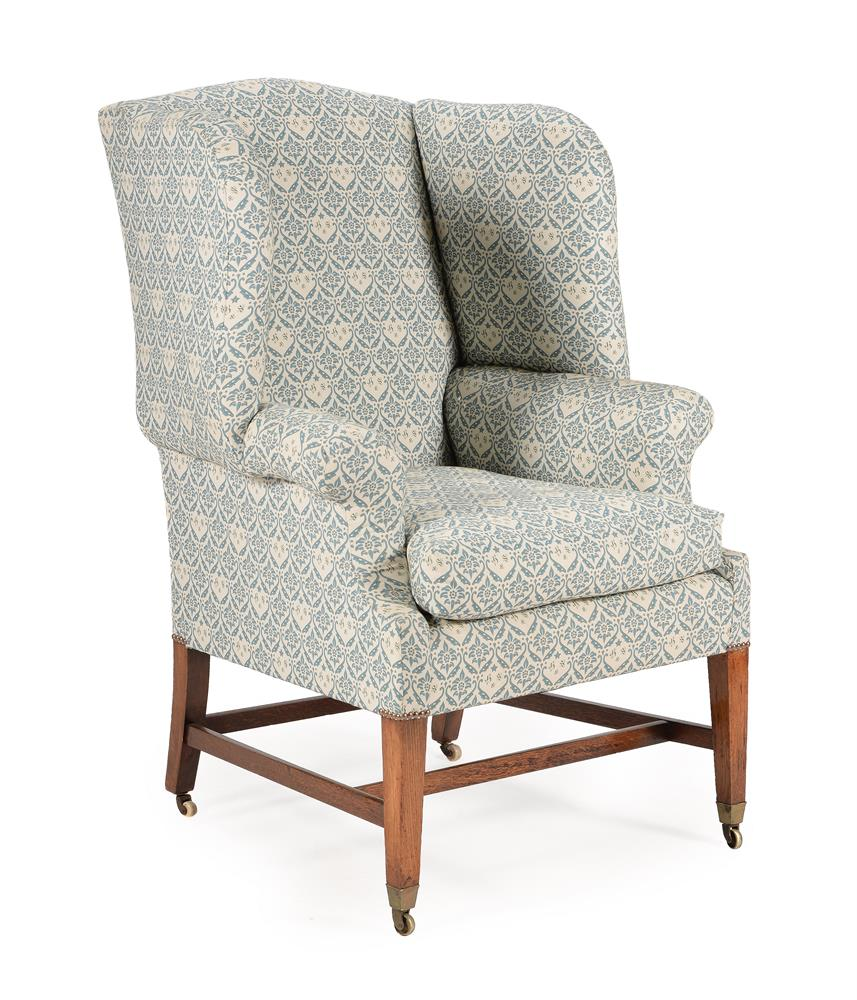 AN EDWARDIAN OAK, SIMULATED OAK AND UPHOLSTERED WING ARMCHAIR, EARLY 20TH CENTURY
