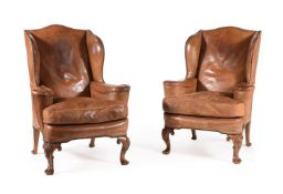 A PAIR OF WALNUT AND LEATHER UPHOLSTERED WING ARMCHAIRS, IN GEORGE II STYLE