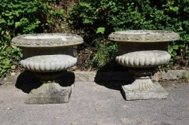 A PAIR OF COMPOSITION STONE PEDESTAL URNS, IN THE MANNER OF AUSTIN & SEELEY, EARLY 20TH CENTURY