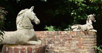 A PAIR OF COMPOSITION STONE MODELS OF RECUMBENT HORSES, POSSIBLY HERALDIC FINIALS, 20TH CENTURY