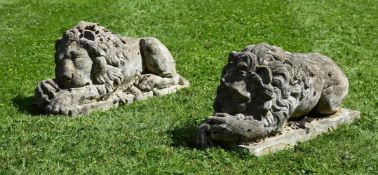 A PAIR OF COMPOSITION STONE MODELS OF RECUMBENT LIONS, 20TH CENTURY