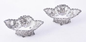 A pair of late Victorian silver shaped oval pedestal sweet baskets by James Dixon & Sons
