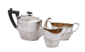 A matched Edwardian silver three piece oval half reeded three piece tea service by Joseph Rodgers &