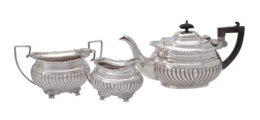 An Edwardian silver three piece oblong half lobed tea set by George Nathan & Ridley Hayes