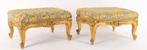 A pair of early Victorian giltwood footstools
