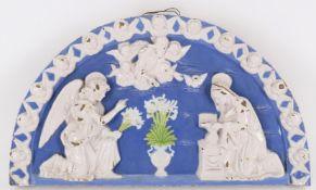 A glazed terracotta lunette depicting The Annunciation after Andrea Della Robbia