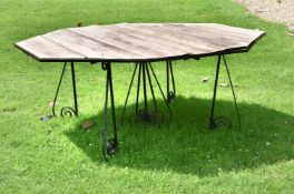 A large wrought iron and wood garden table
