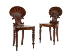 A pair of George IV carved oak shell-back hall chairs