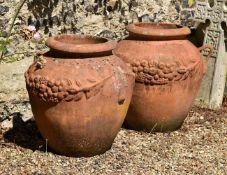 A large pair of terracotta twin handled garden urns