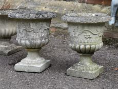 A pair of composition stone urns
