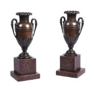 A pair of bronzed metal urns in Empire style