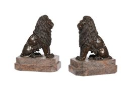 A pair of bronze models of seated lions