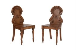 A pair of Victorian oak hall chairs