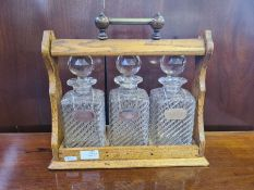 An oak 3 bottle tantalus with Old Hall stainless spirit labels. Lock missing.