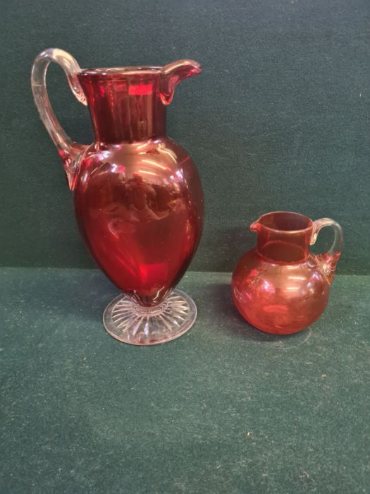 """Large Victorian cranberry glass jug with clear cut foot standing 11"""" tall and a similar smaller"""