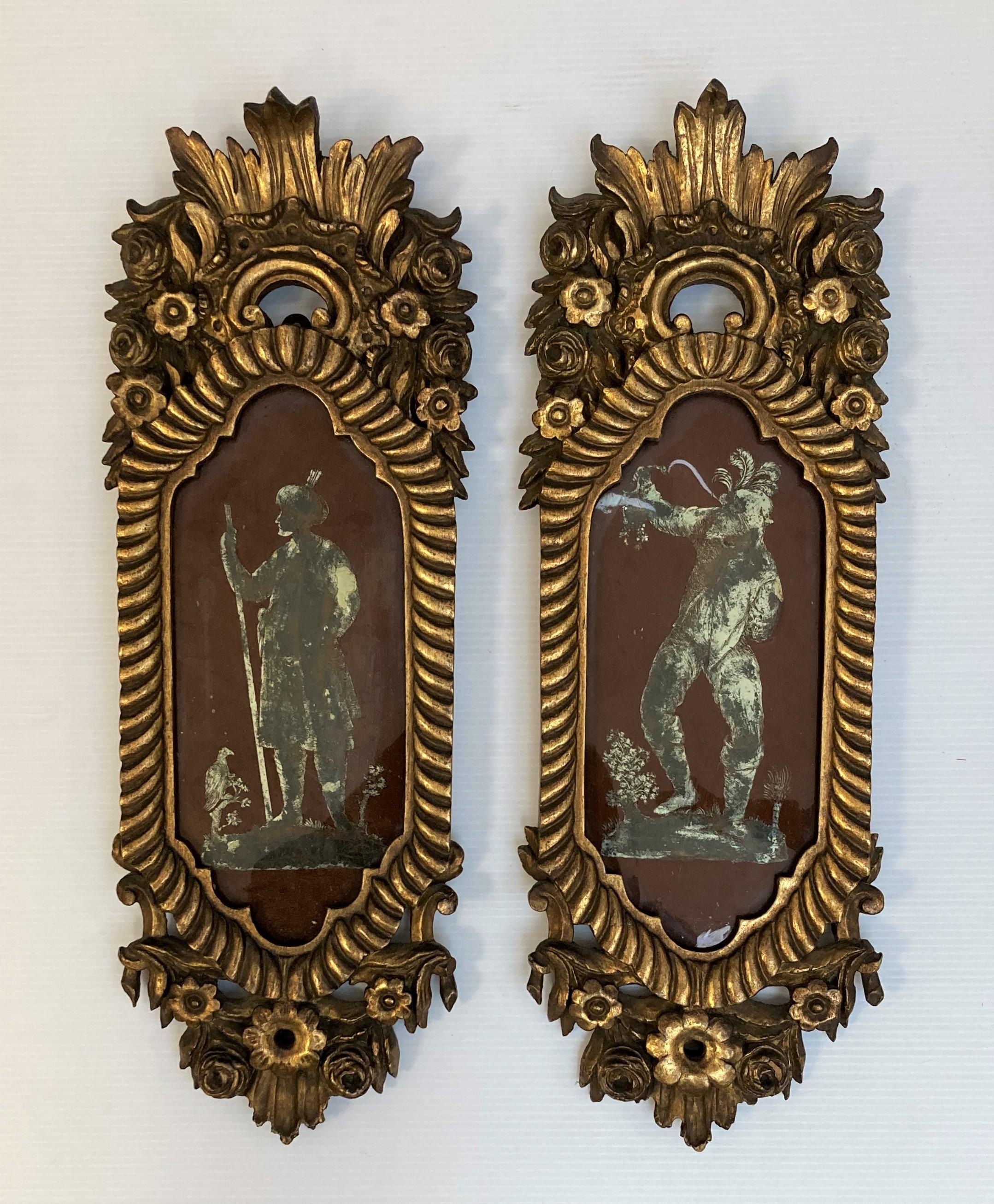 Paire de FIXES sous verre figurant des personnages costumés. Encadrements en bois sculpté et doré.