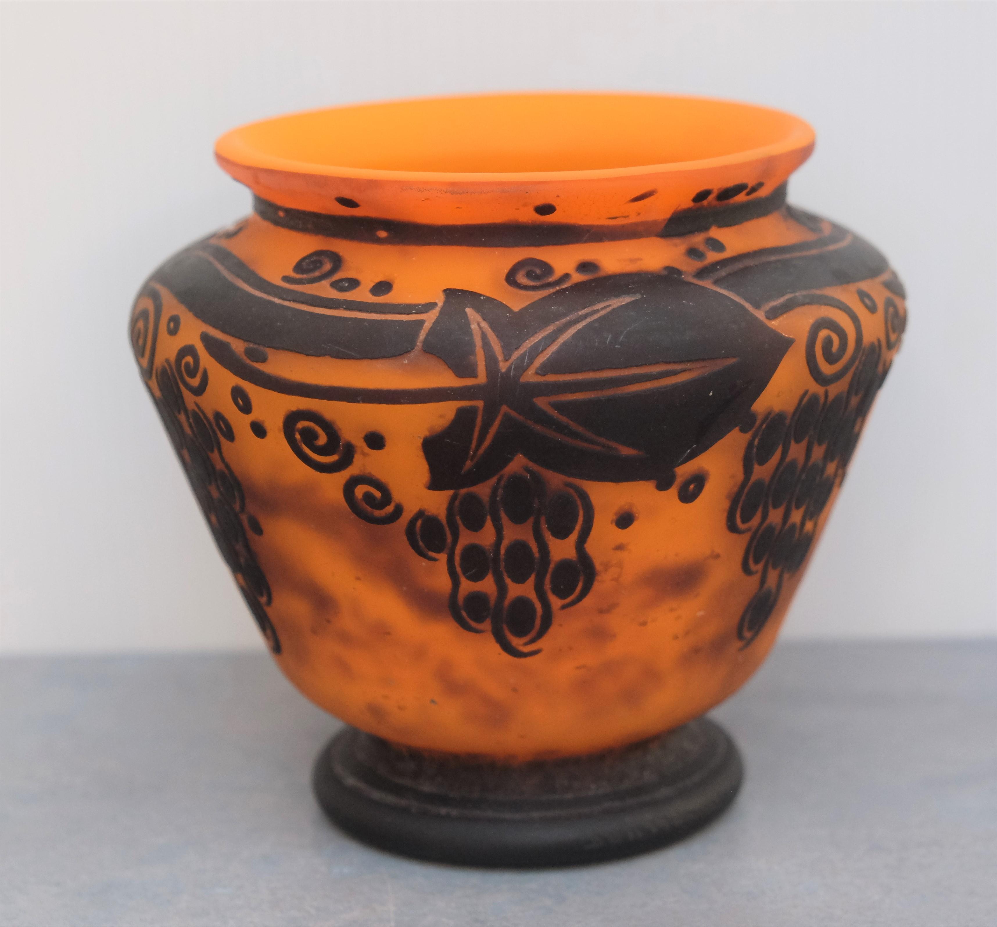 VASE en verre gravé à l'acide de motifs de glycines brunes sur fond orange. Signé DAUM Nancy. Epoque