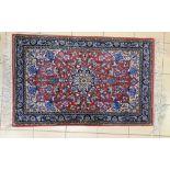 TAPIS à décor floral sur fond rouge. Iran, XXe. 112 X 70.