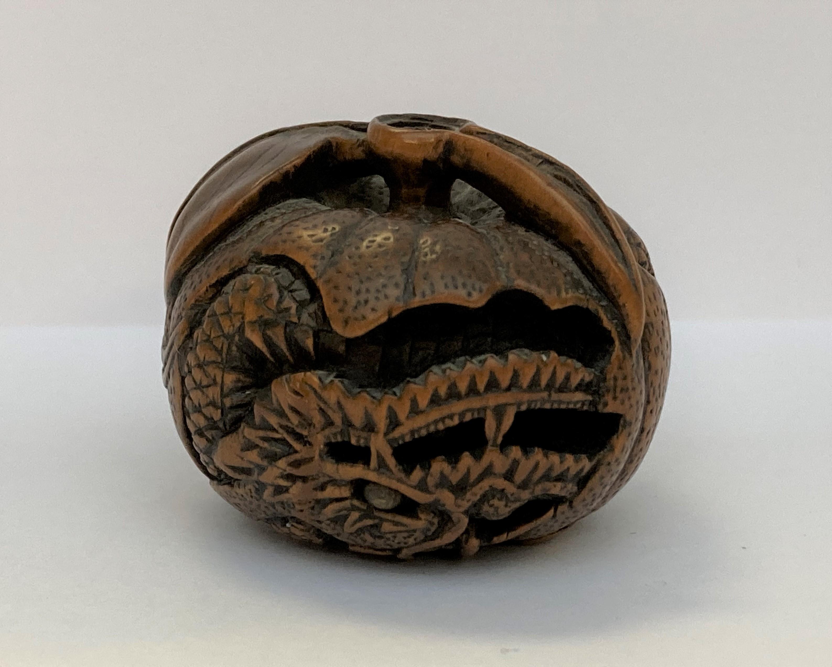 NETSUKE en buis figurant un dragon enroulé sur lui-même dans un mikan, son oeil visible incrusté