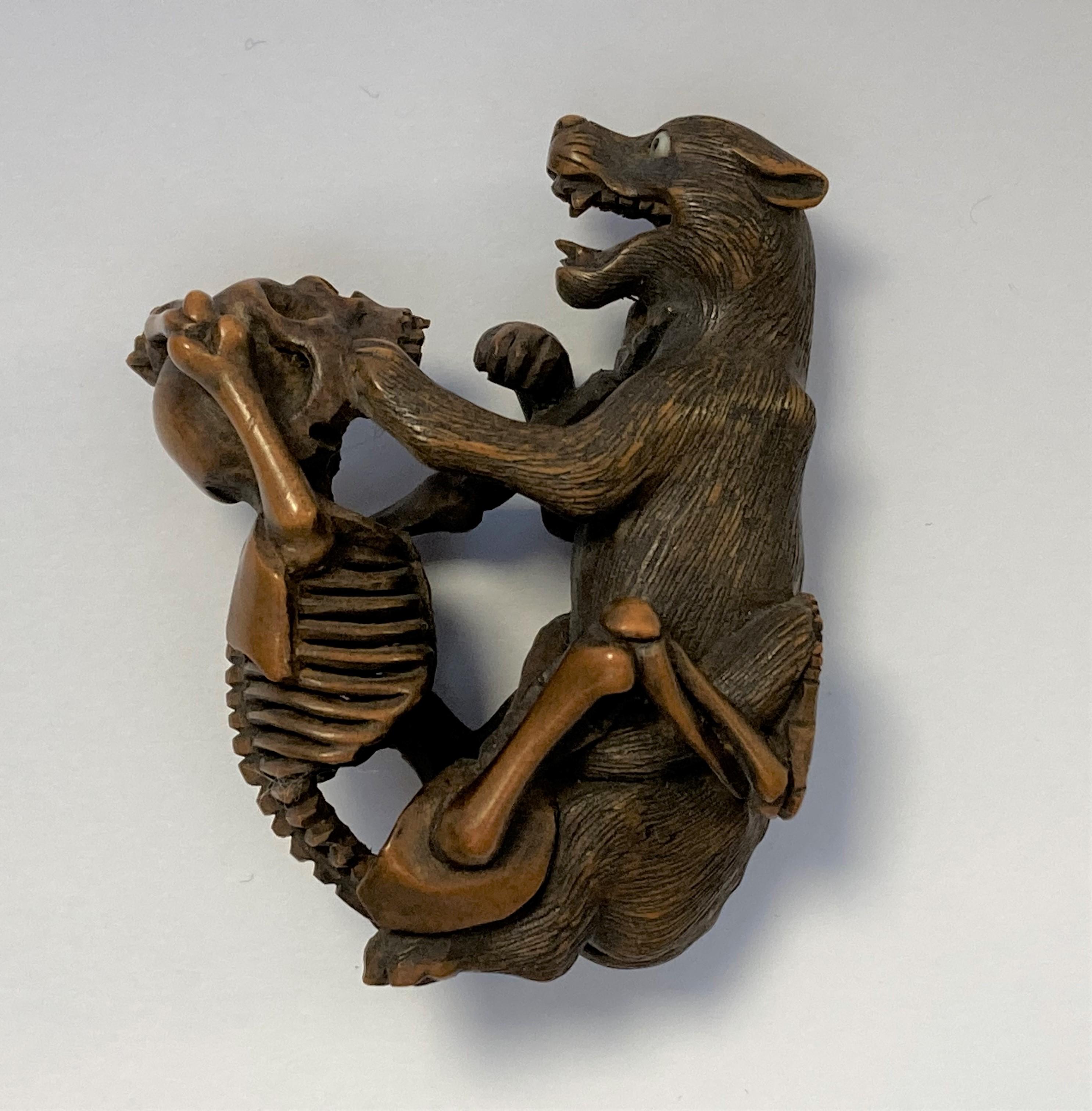 NETSUKE en bois figurant un squelette et un loup combattant, la main du squelette sur la gorge de