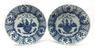 Pair of 18th century Delft blue and white chargers, centrally painted with a vase of flowers, the bo