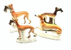 Three 19th century Staffordshire Greyhound models holding a in their mouths and another with pen sta