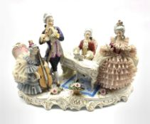 German porcelain musical figure group, comprising a seated gentleman playing a piano, a standing gen