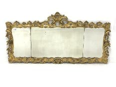 Mid 19th century giltwood wall mirror, with carved and pierced foliate enclosing three bevelled plat