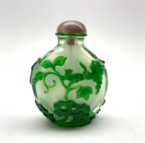 Chinese Peking glass snuff bottle of flat ovoid form, decorated in green glass overlay depicting a s