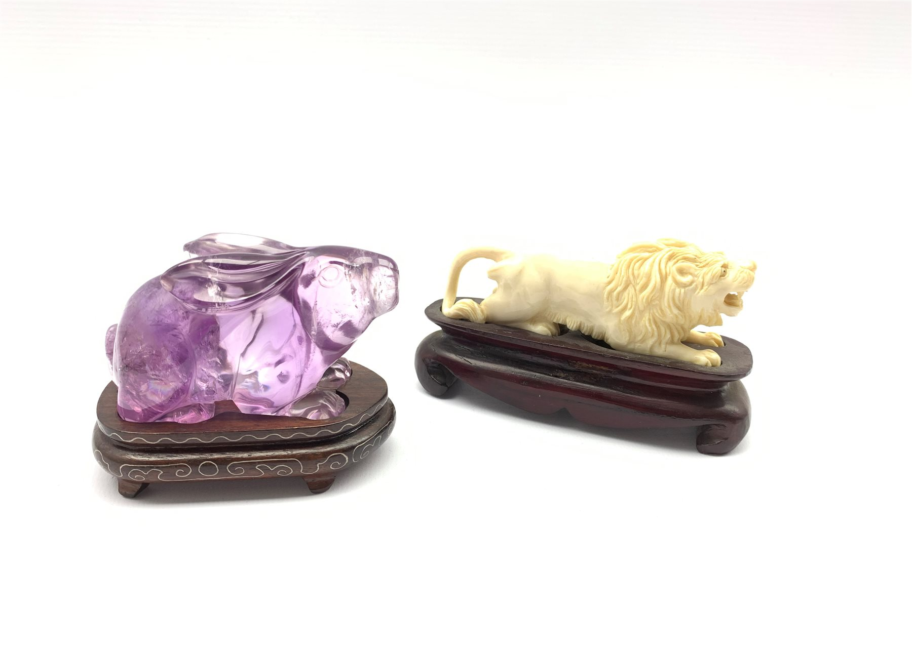 Oriental amethyst glass rabbit on a wooden stand W9cm and an early 20th century carved ivory figure