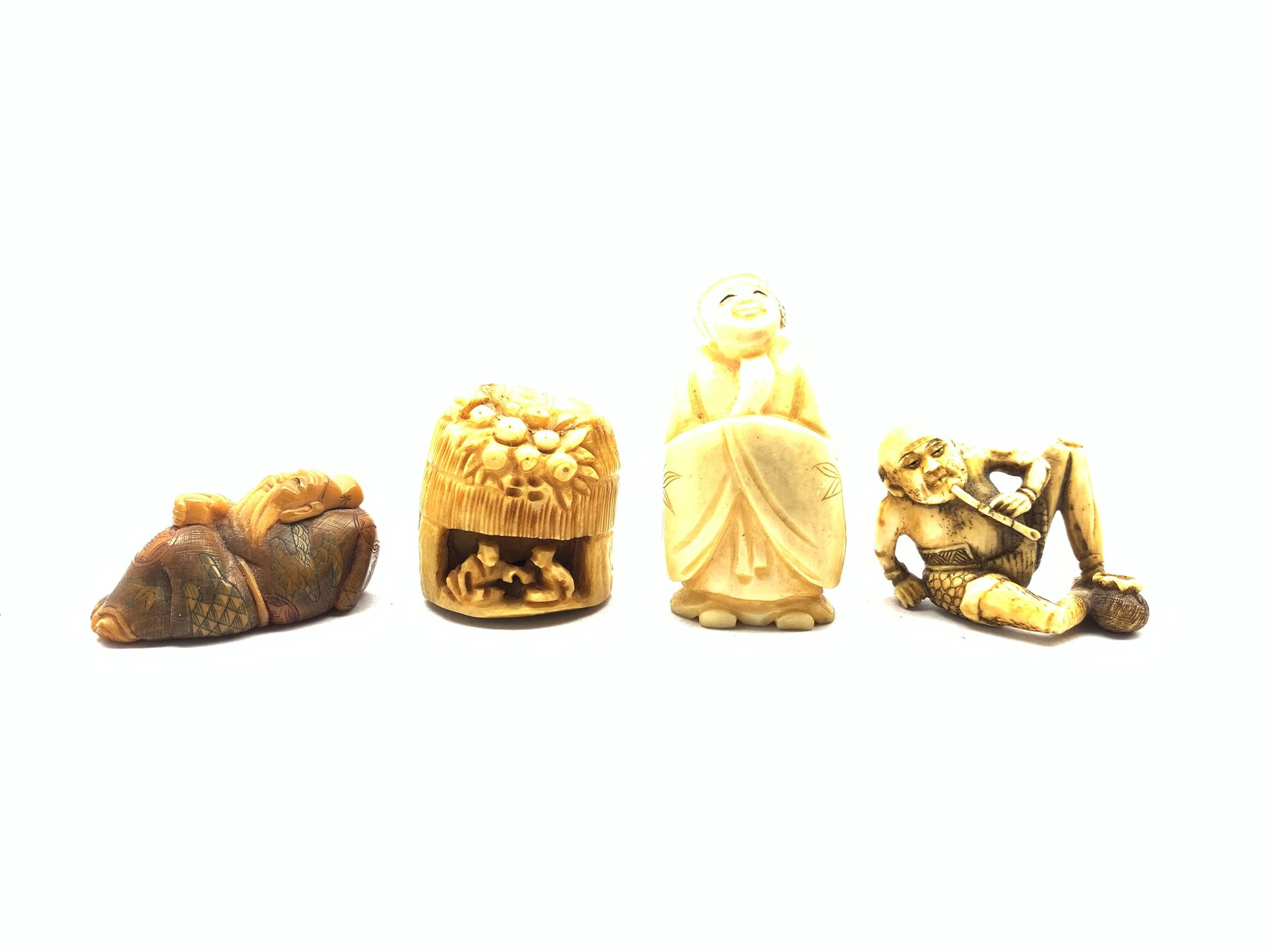Group of early 20th century Japanese Netsukes comprising a carved ivory figure of a Scholar wearing