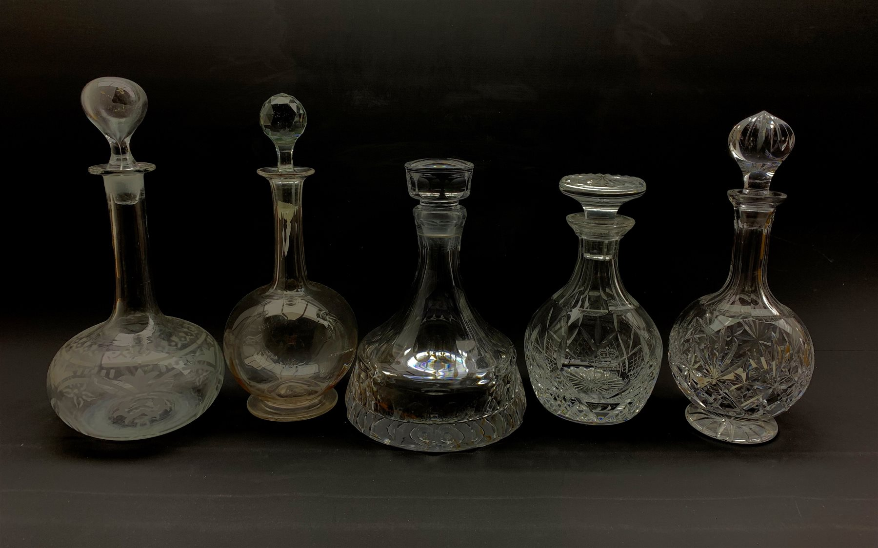 Five glass decanters comprising a heavy slice cut ships decanter, unmarked, Stuart mallet form decan