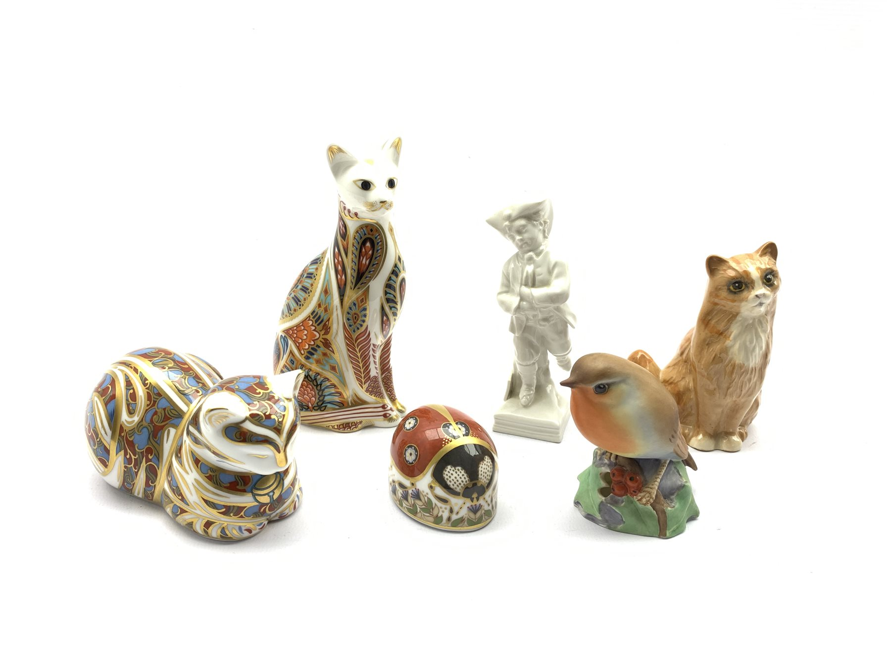 Berlin white glazed porcelain figure ice skating on square base H11cm, three Crown Derby paperweight