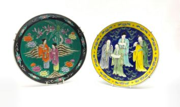 Japanese plate decorated with figures within a yellow floral border and another similar in black fl