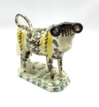 19th century Pratt type cow creamer sponged in black and yellow with seated milk maid on an octagona